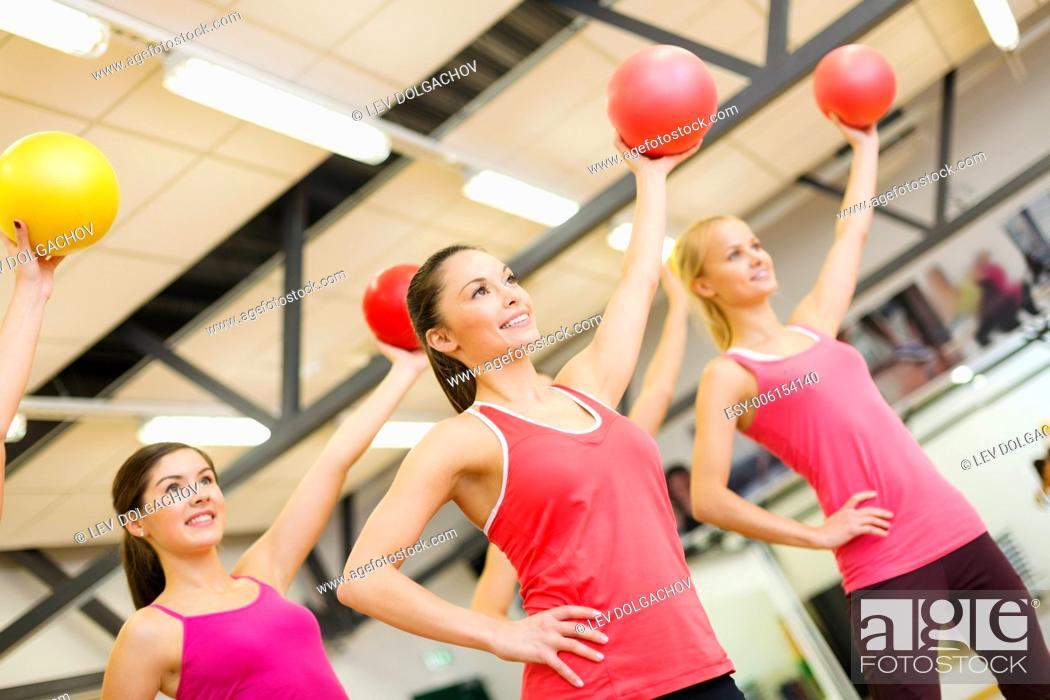 Stock Photo: fitness, sport, training, gym and lifestyle concept - group of smiling people working out with stability balls in the gym.