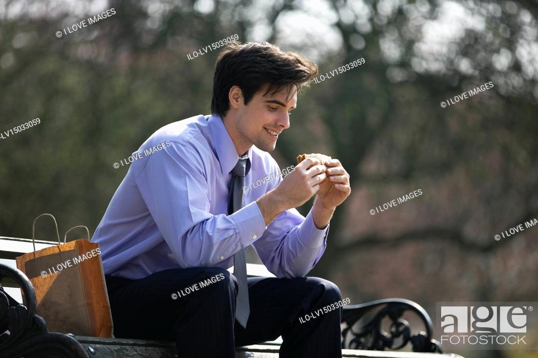 Stock Photo: A businessman sitting on a bench, eating a sandwich.