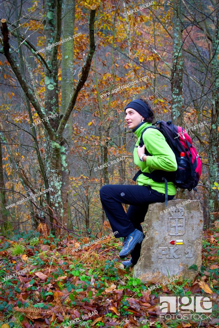 Stock Photo: Woman over a road signal  Sobrescobio  Alba river route  Redes Natural Park, Asturias, Spain.