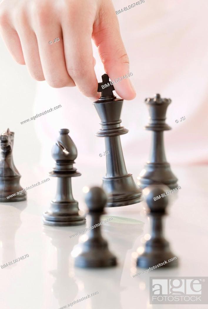 Stock Photo: Woman moving chess piece.