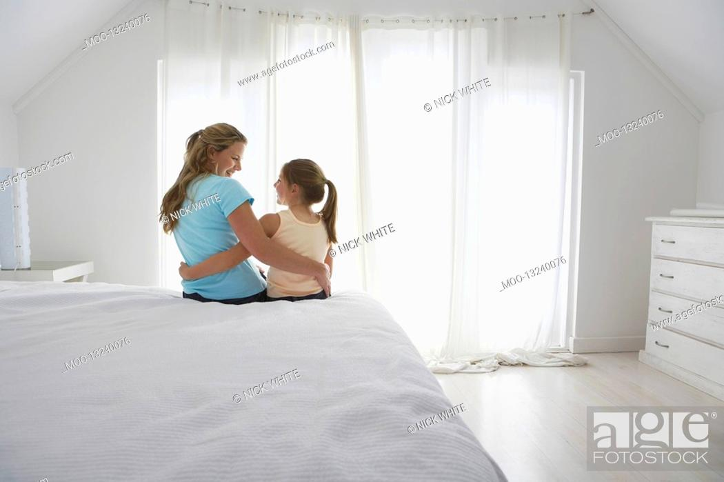 Stock Photo: Mother and daughter sitting on bed in bedroom.