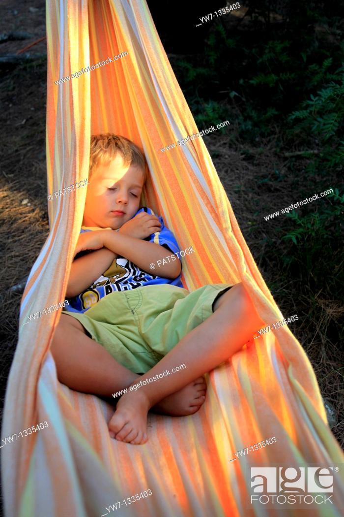 Stock Photo: Boy aged 4 resting in a hammock.