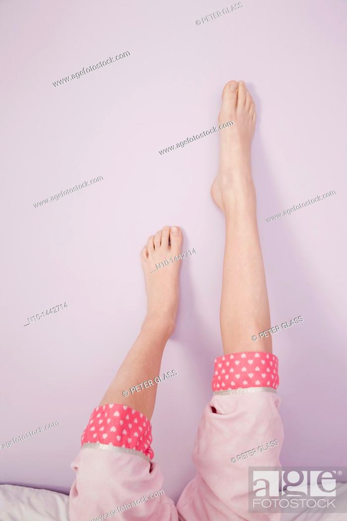 Stock Photo: Preteen girl's legs and feet resting on a wall.