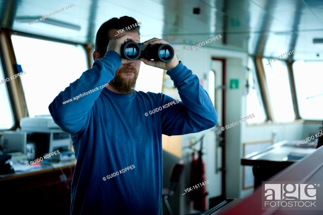 Stock Photo: The captain of the container-vessel MV Flintercape uses binoculars to spot for other ships in the vicinity, during the voyage from Rotterdam.