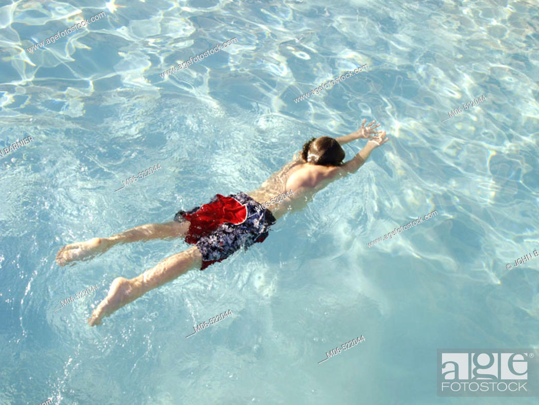 Stock Photo: Boy swimming underwater in a swimming pool.