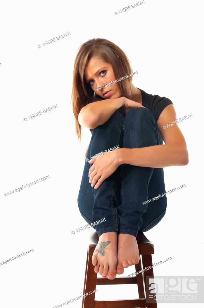 Stock Photo: Portrait of young sexy woman sitting on a stool.