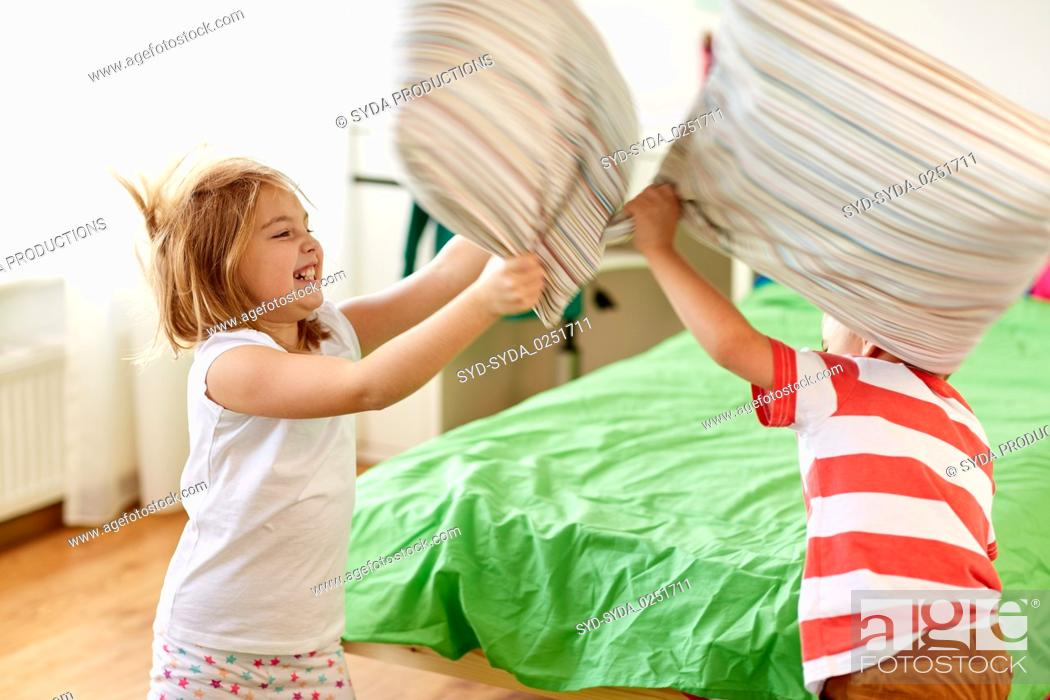 Stock Photo: kids playing and fighting by pillows at home.