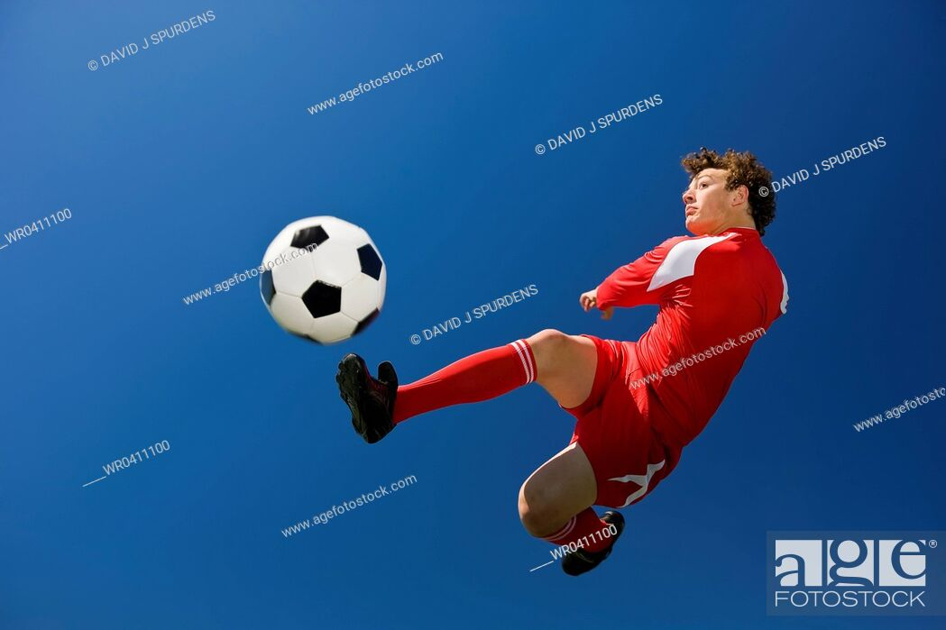 Stock Photo: A soccer player volleys a ball in mid air.