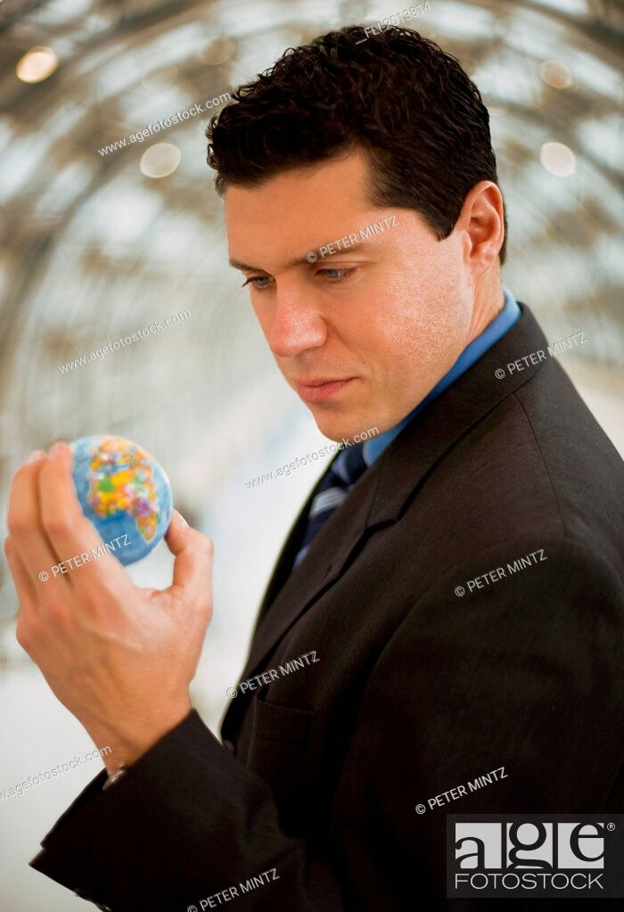 Stock Photo: Business Man Holding The World In His Hand.
