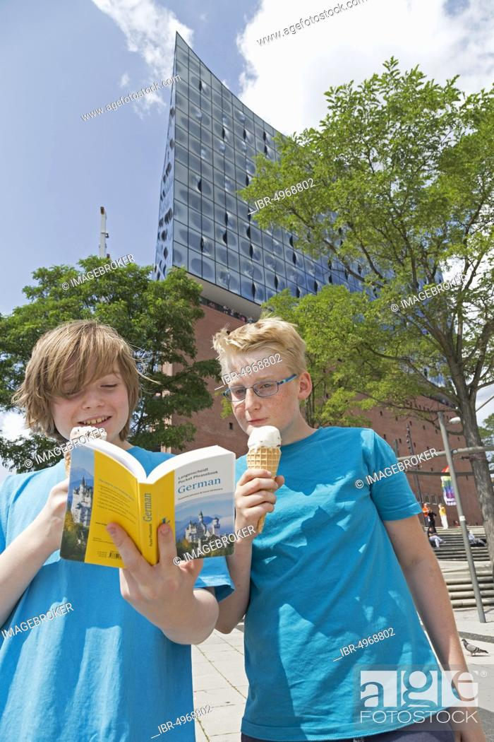 Imagen: Young people on a language trip study a dictionary in front of the Elbe Philharmonic Hall, Hamburg, Germany, Europe.