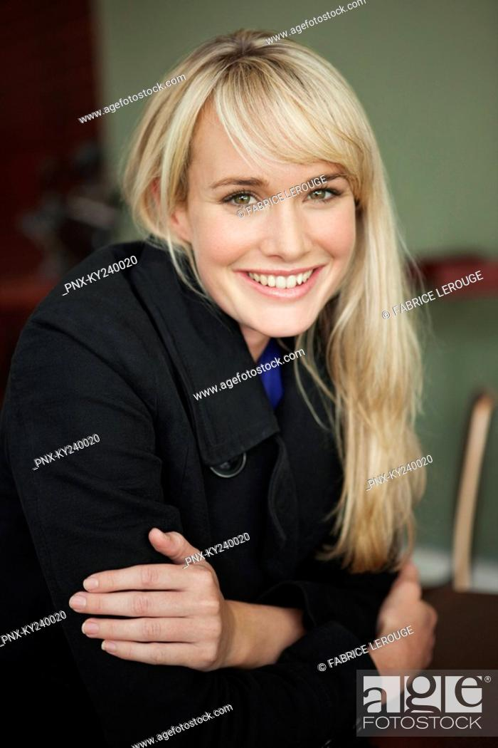 Stock Photo: Woman sitting in a cafe and smiling.