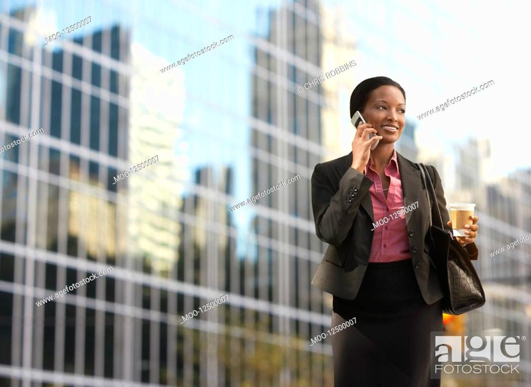Stock Photo: Businesswoman using mobile phone outside office building.