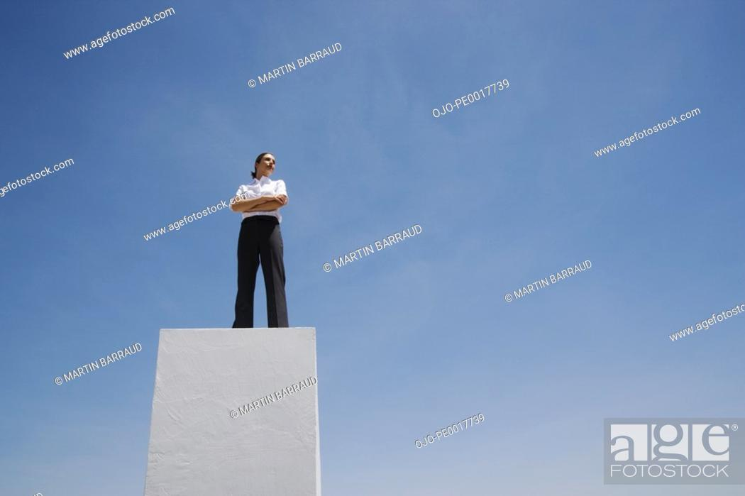 Stock Photo: Businesswoman standing on pedestal outdoors.