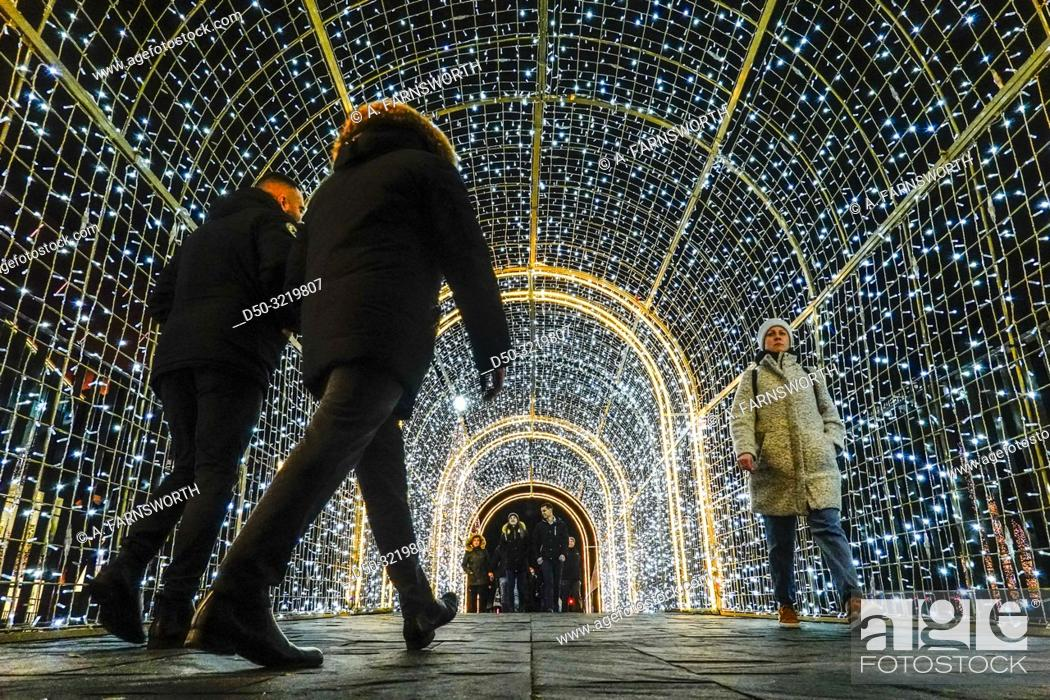 Stock Photo: Gdansk, Poland Christmas decorations in a light tunnel at the Forum Mall and pedestrians.