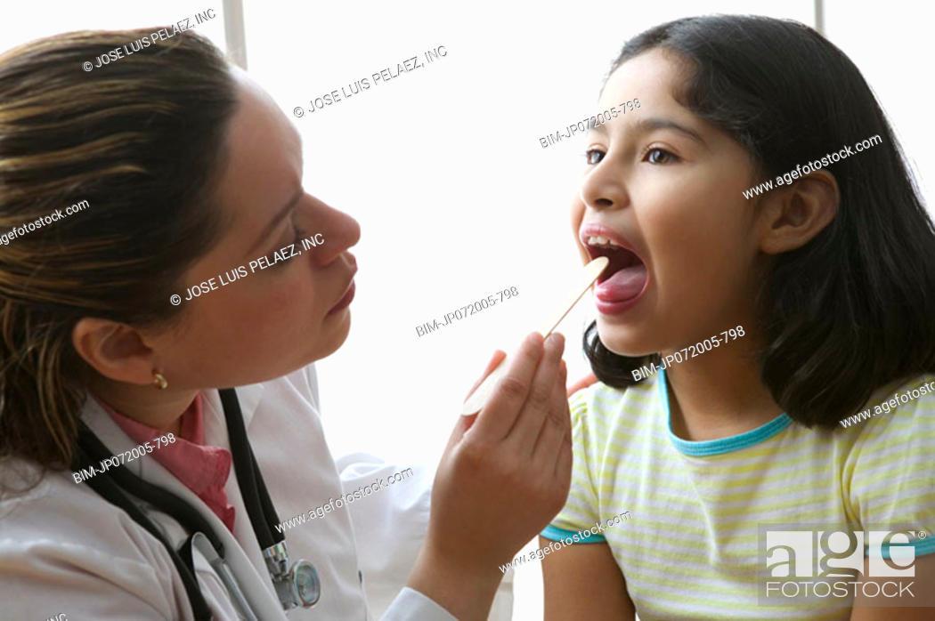 Stock Photo: Female doctor checking girl's tonsils.