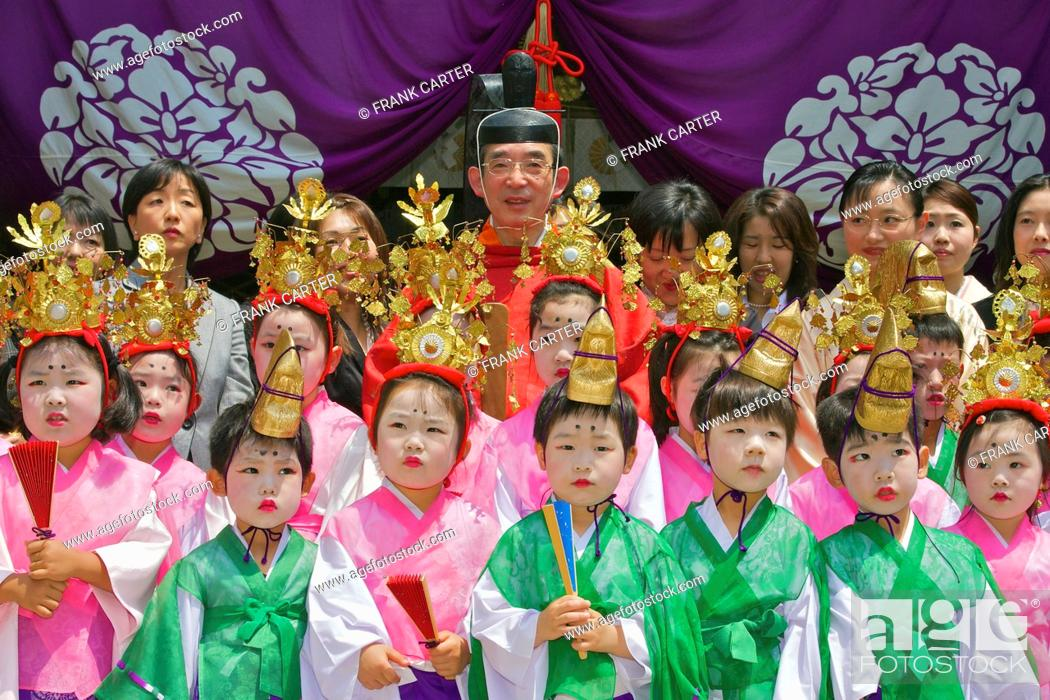 Stock Photo: A group portrait of costumed children with a priest and mothers behind.