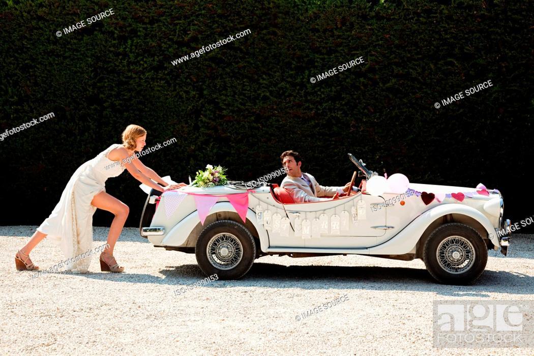 Stock Photo: Bride pushing broken down vintage car.
