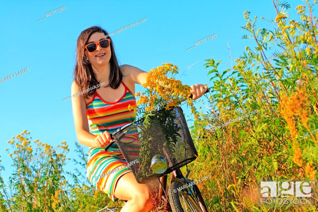 Stock Photo: A pretty, young woman on a bike with wildflowers in the meadow.
