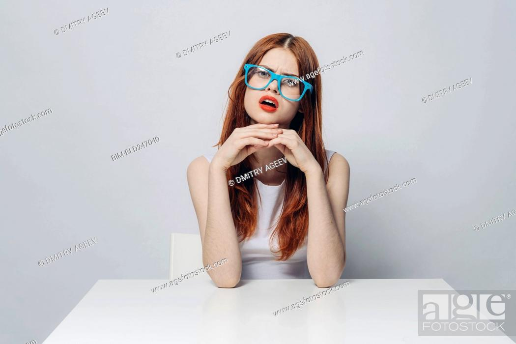 Stock Photo: Angry Caucasian woman sitting at table wearing blue eyeglasses.