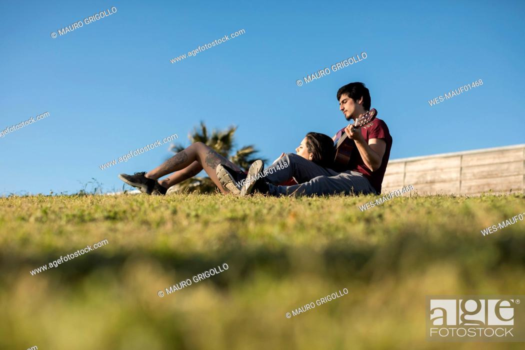 Imagen: Young couple playing guitar on a meadow.