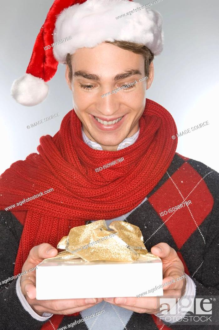 Stock Photo: Young man holding a christmas gift.