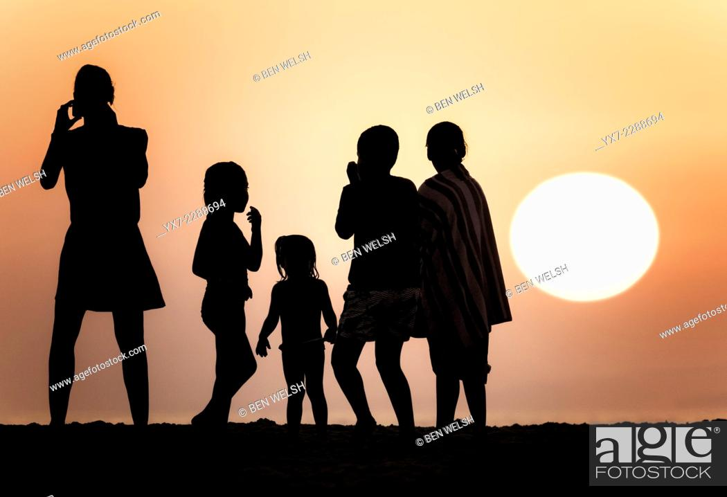 Stock Photo: Silhouettes of people against a sunset.