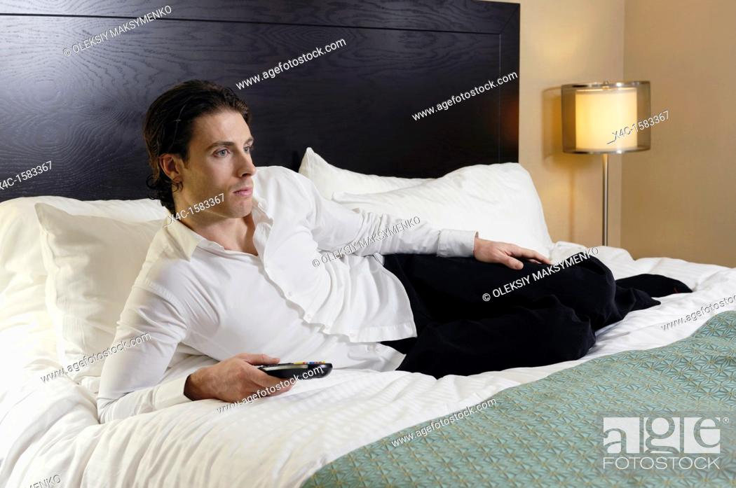 Stock Photo: Young man with a remote control lying alone on a bed and watching TV.