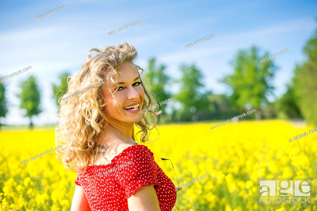 Stock Photo: Smiling mature woman wearing red dress standing against oilseed rapes.