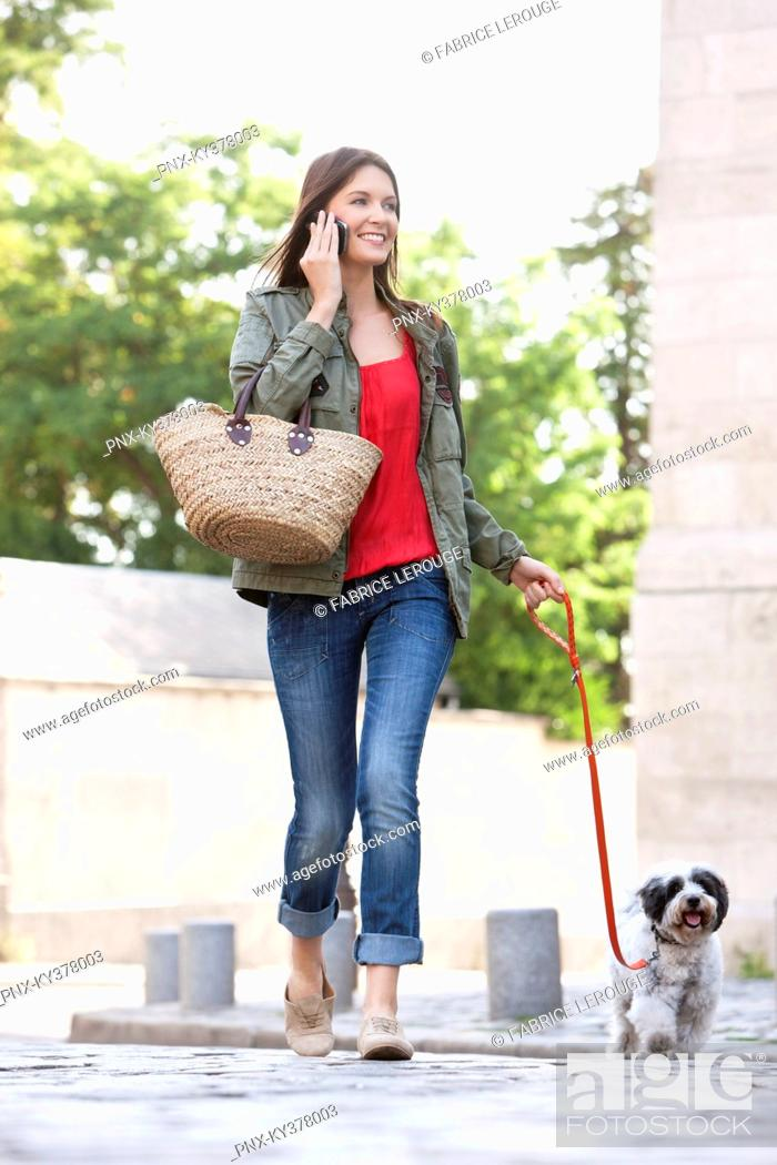 Stock Photo: Woman holding a puppy on leash while talking on a mobile phone, Paris, Ile-de-France, France.