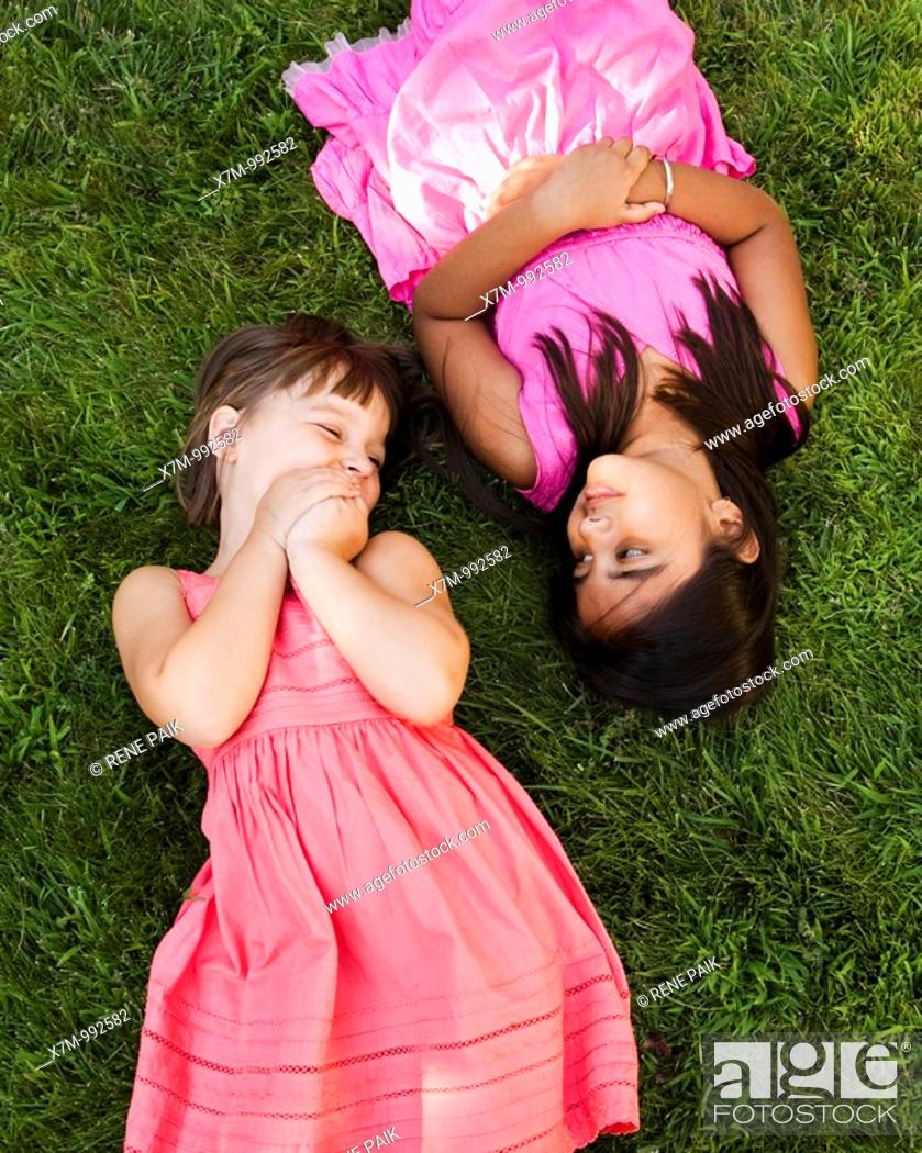 Stock Photo: A little caucasian girl and an Asian Indian girl lay in the grass to relax and play.