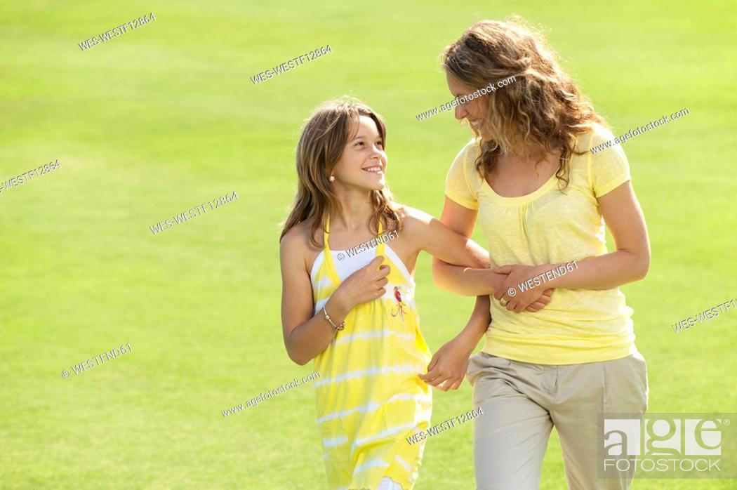 Stock Photo: Spain, Mallorca, Mother and daughter 10-11 walking across meadow.
