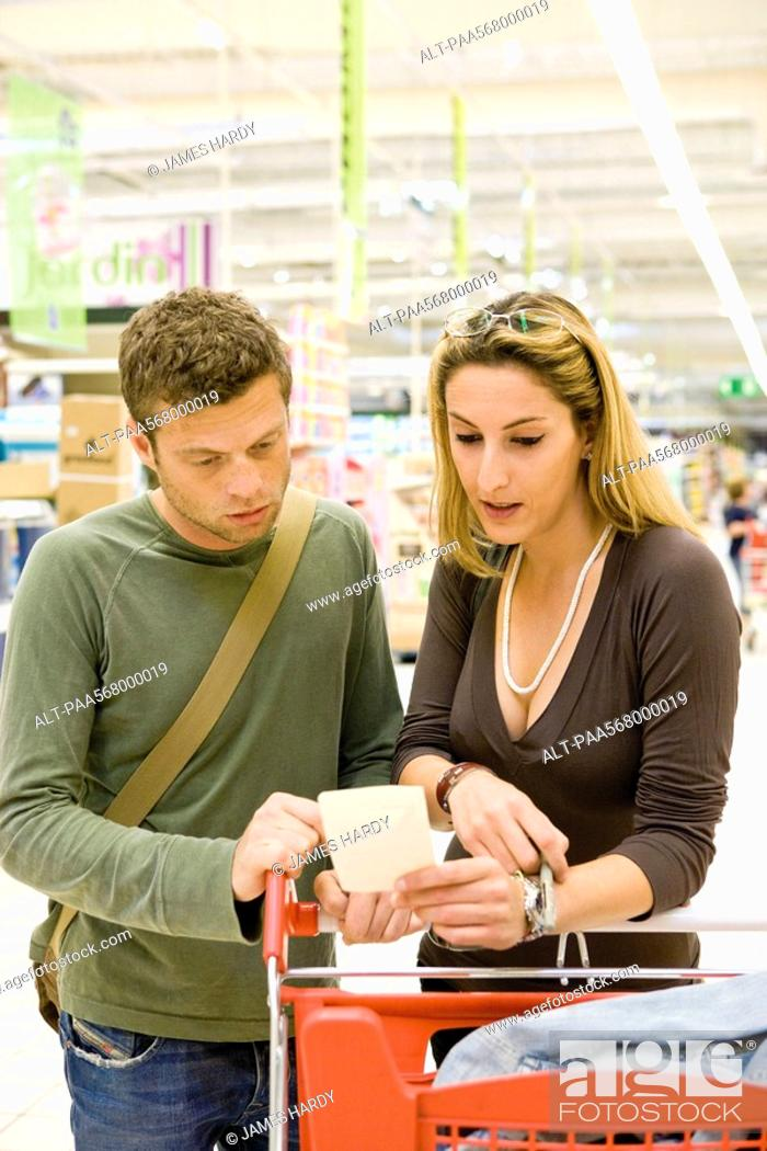 Stock Photo: Couple with shopping cart reviewing receipt.
