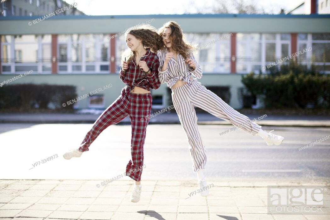 Imagen: two happy women jumping against each other, wearing pyjamas at street.