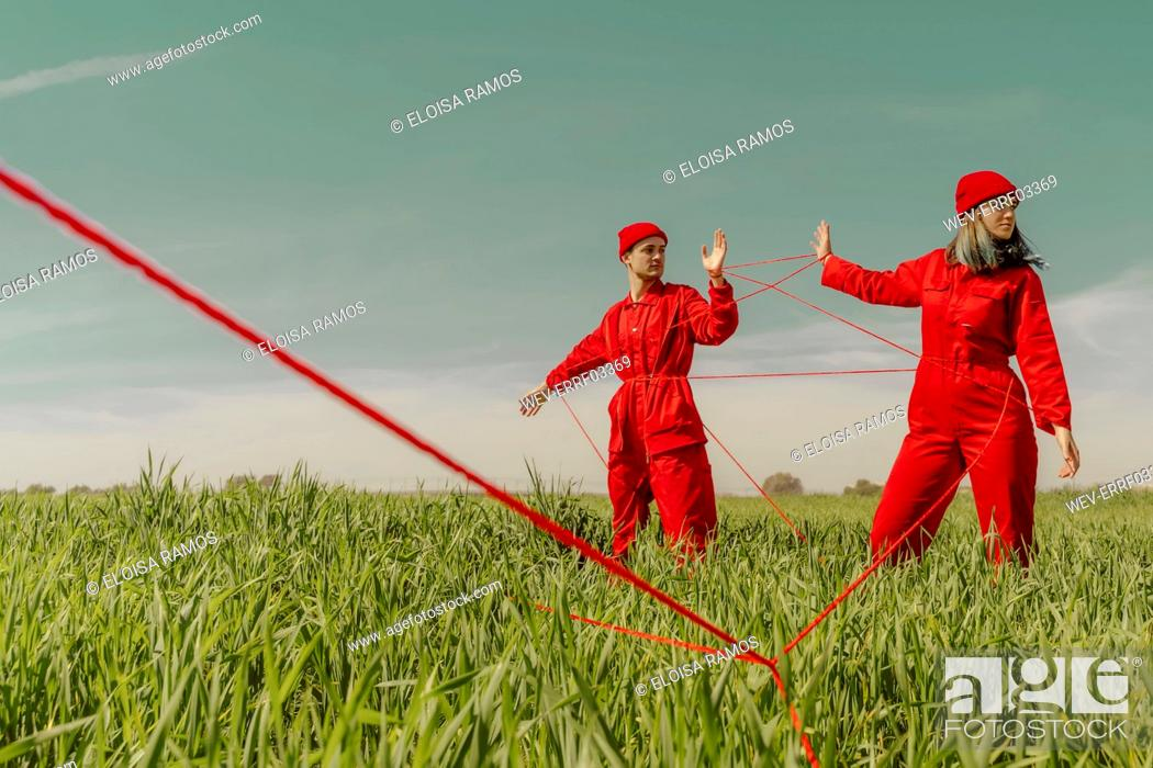 Stock Photo: Young couple wearing red overalls and hats performing on a field with red string.