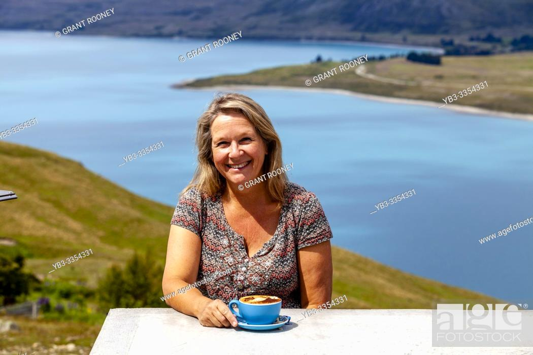Imagen: A Middle Aged Woman Sitting With A Cup Of Coffee Overlooking Lake Tekapo, Mt John Observatory Viewpoint, Mackenzie District, South Island, New Zealand.