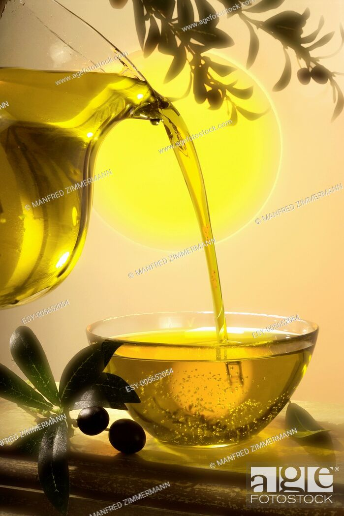 Stock Photo: golden Olievenoel flows from glass jug in glass bowl.