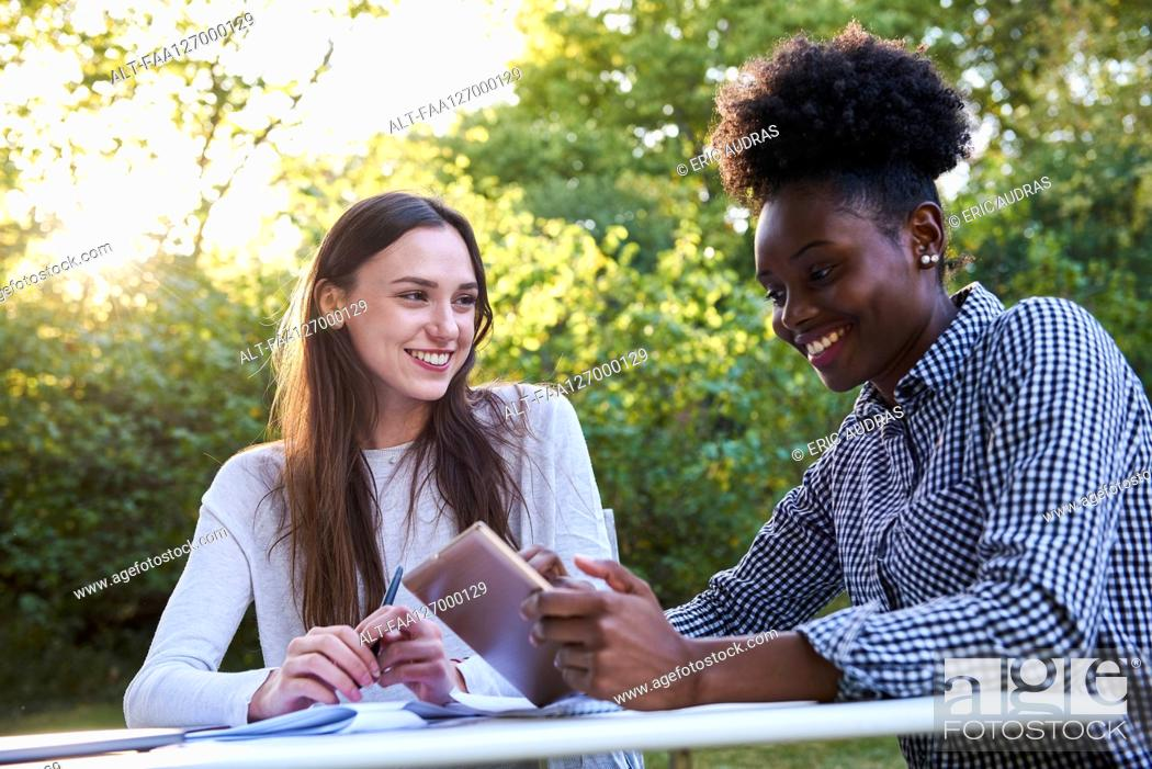 Photo de stock: Smiling young friends using digital tablet while studying in park, Orgeval.