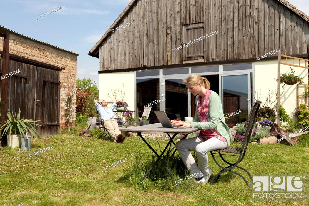 Stock Photo: A woman using a laptop and having breakfast in her backyard.