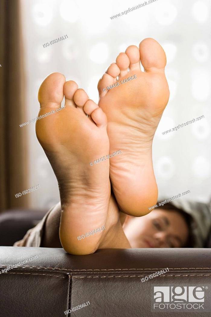 Stock Photo: Feet of woman on sofa.