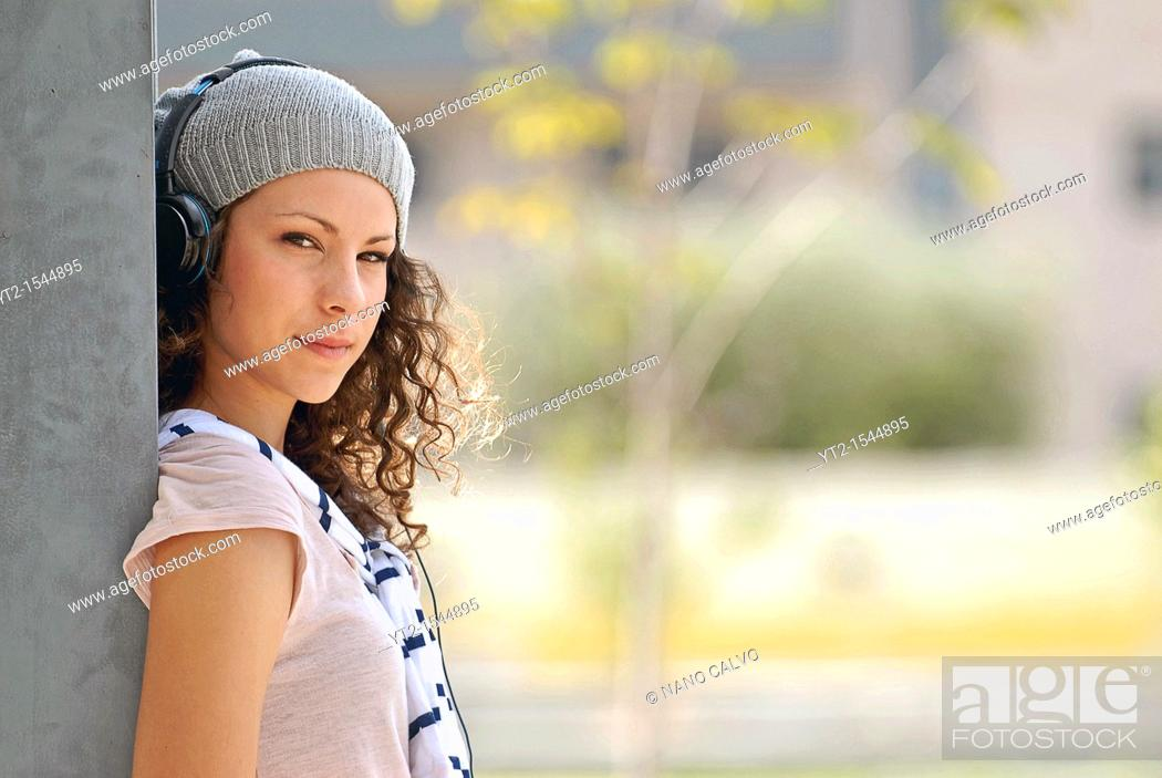 Stock Photo: Cute young woman listening music with headphones.