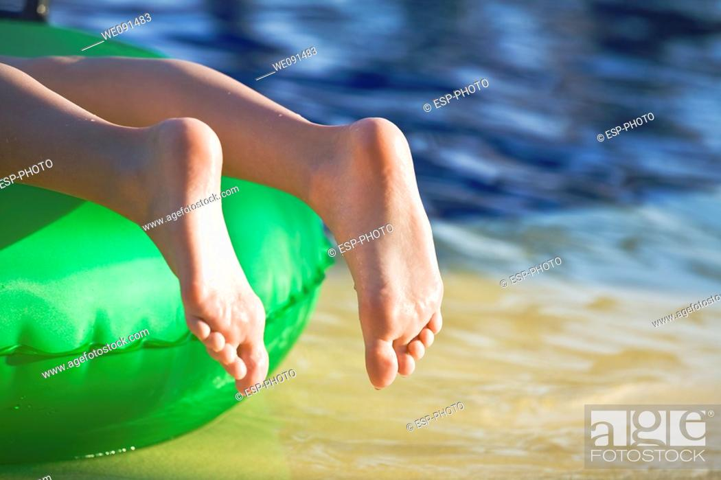 Stock Photo: Young girl lying on green float with toes pointed at waters edge.