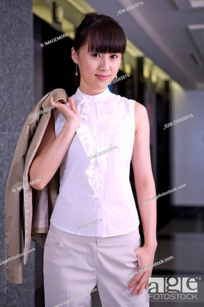 Stock Photo: Young woman standing with hand in pocket and looking at the camera.