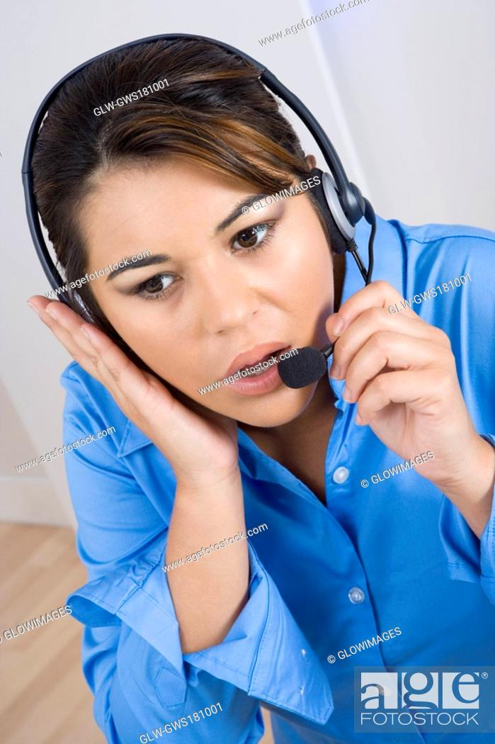 Stock Photo: Close-up of a businesswoman wearing a headset and looking away.