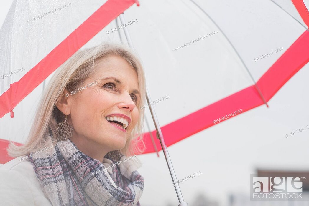 Stock Photo: Older Caucasian woman standing under umbrella.