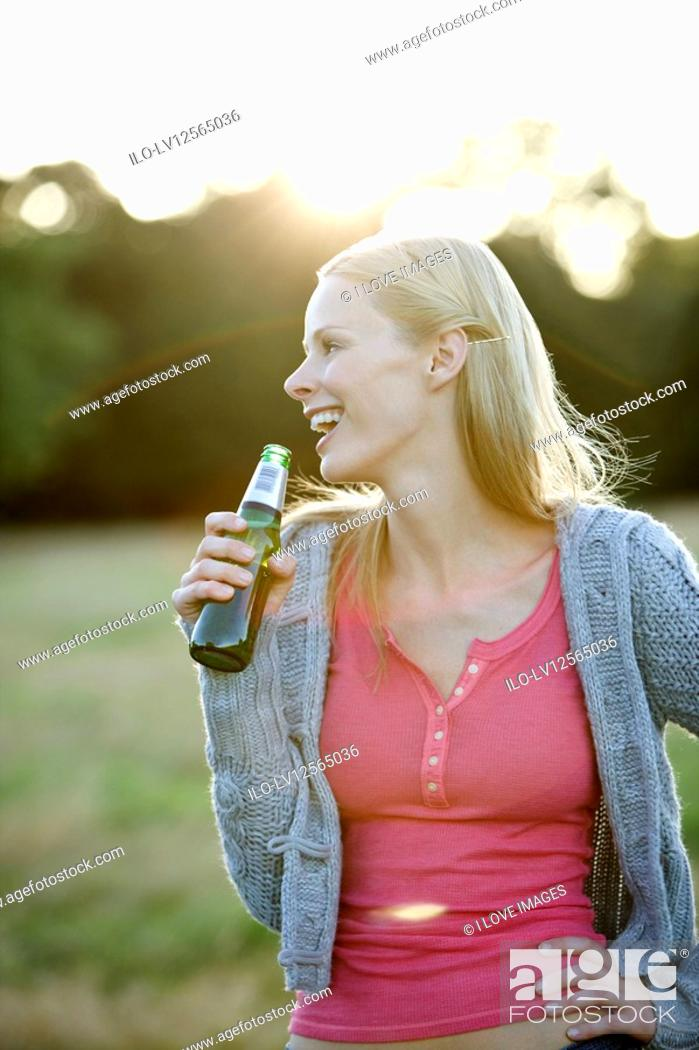 Stock Photo: Portrait of a young woman drinking a beer outdoors.