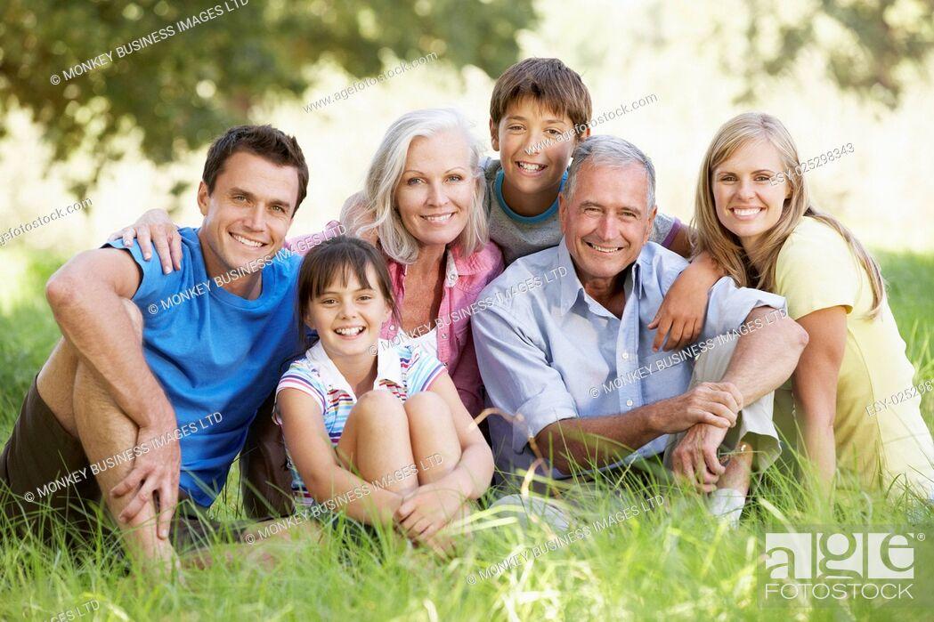 Photo de stock: Three Generation Family Relaxing In Summer Field.