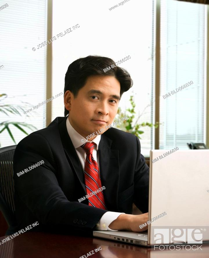 Stock Photo: Chinese businessman typing on laptop.