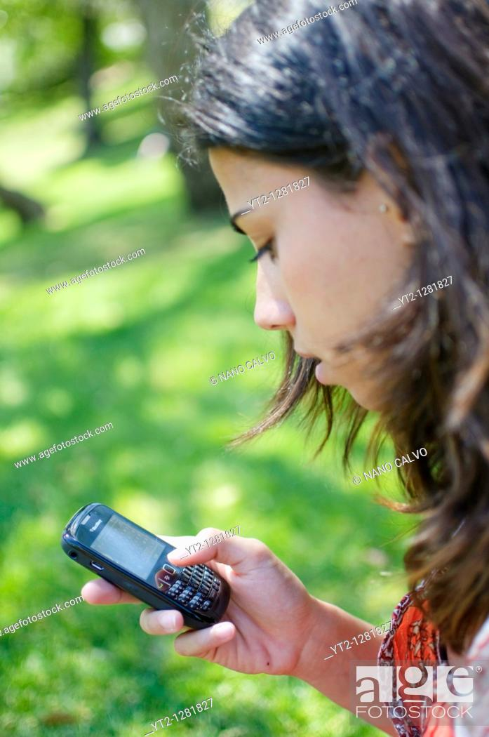 Stock Photo: Young girl using her Blackberry mobile phone, Madrid, Spain.