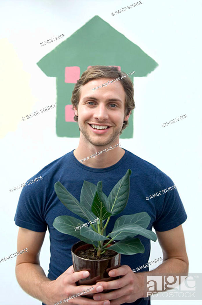 Stock Photo: Man holding a house plant.