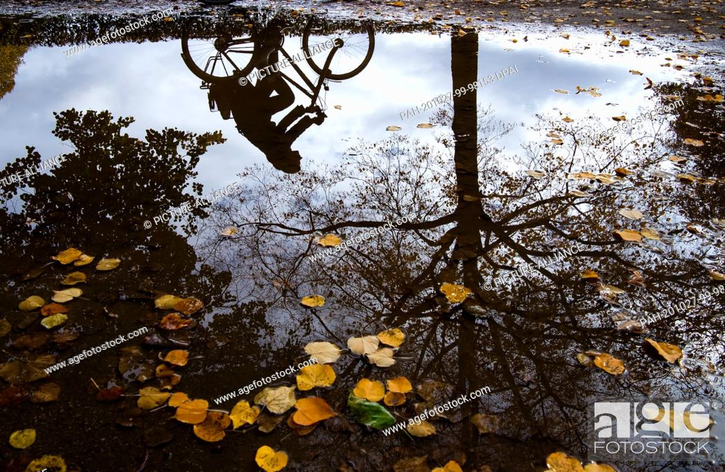 Stock Photo: 27 October 2020, Bavaria, Munich: A cyclist is reflected in a large puddle in the Hofgarten behind the Bavarian State Chancellery in the heart of the Bavarian.